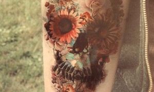 Girl's arm painted beautiful flowers and creative 骷髅 tattoo picture